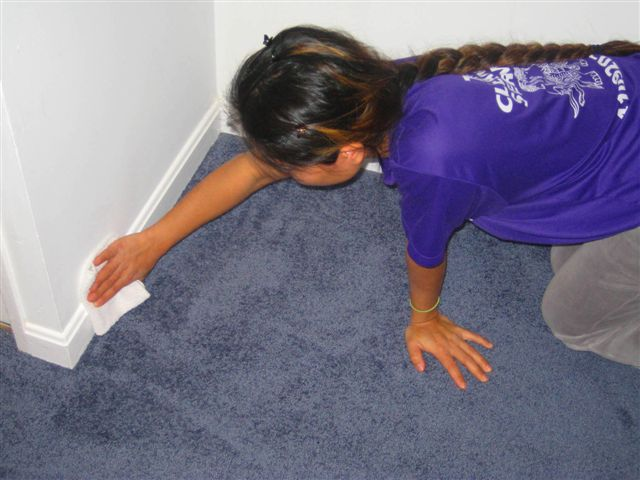 Woman cleaning the wall molding